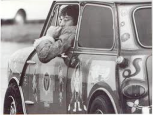 John Lennon sitting in George Harrison's custom painted Mini